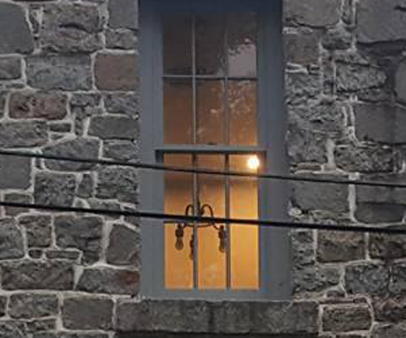 Face in the window of the old Princess Anne Jail - Photo by Desiree Wallace
